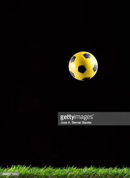Ball of  soccer,  ball bouncing on a surface of  grass Soccer field, on a black bottom
