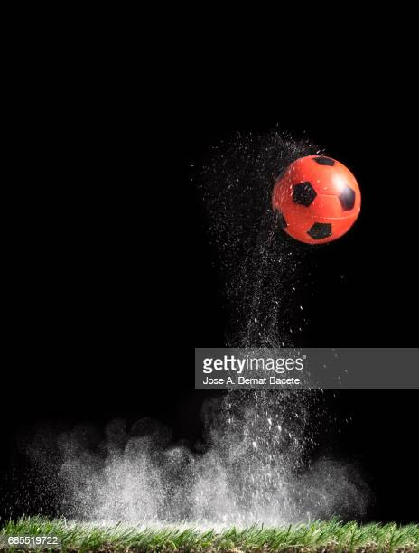 Ball of  soccer ball bouncing on a surface of  grass with a cloud of powder for the impact