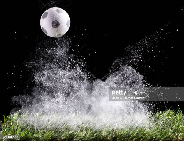 Ball of soccer ball bouncing on a surface of grass with a cloud of powder for the impact Details