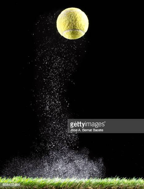 Ball of tennis bouncing on a surface of  grass with a cloud of powder for the impact