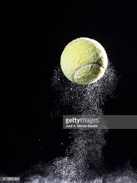 Ball of tennis bouncing on a surface of powder