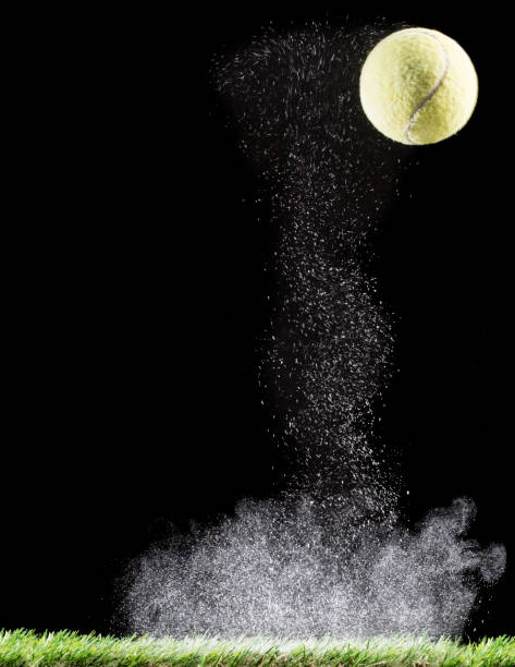 Ball of tennis striking and  bouncing on a surface of powder on a black background