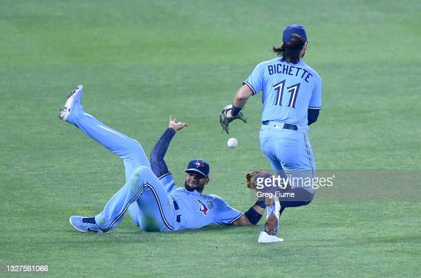 Ball off the bat of Domingo Leyba of the Baltimore Orioles falls between Lourdes Gurriel Jr. #13 and Bo Bichette of the Toronto Blue Jays for a...