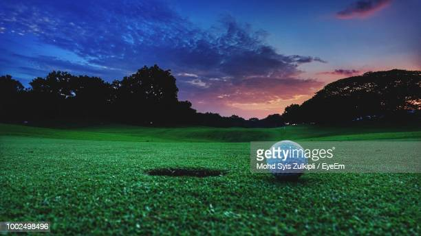 ball on golf course against sky during sunset - golfbaan green stockfoto's en -beelden