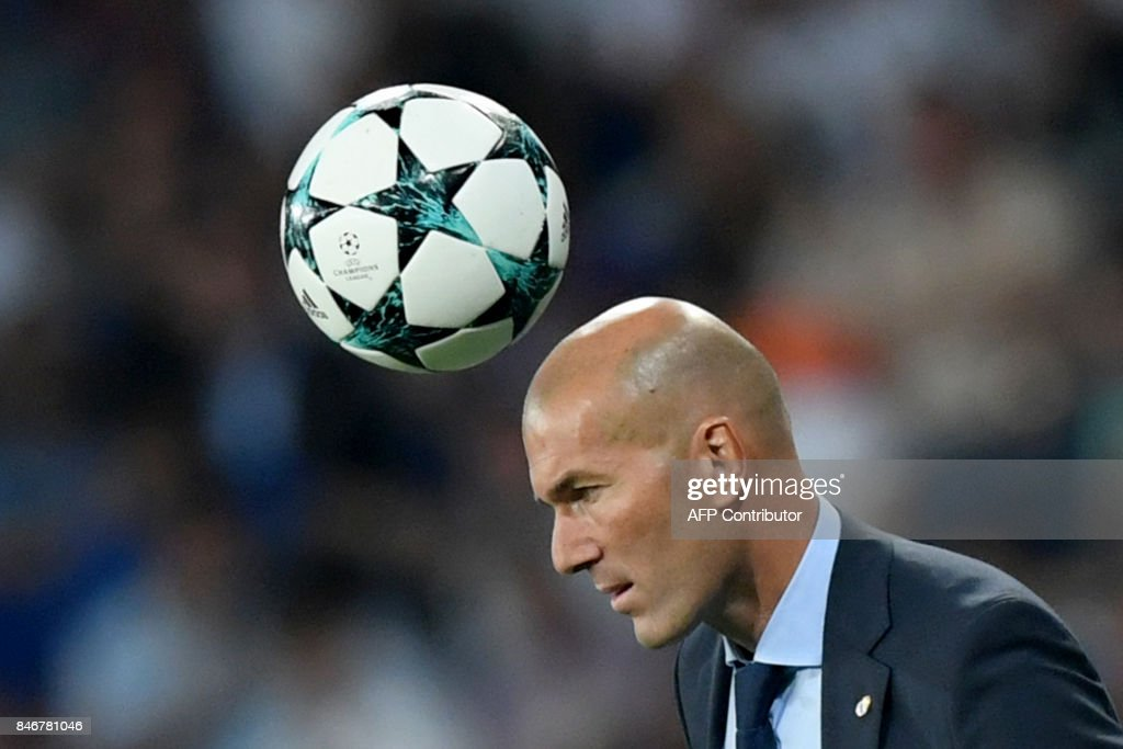 TOPSHOT - A ball passes above Real Madrid's French coach Zinedine Zidane during the UEFA Champions League football match Real Madrid CF vs APOEL FC at the Santiago Bernabeu stadium in Madrid on September 13, 2017. /