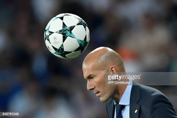 TOPSHOT A ball passes above Real Madrid's French coach Zinedine Zidane during the UEFA Champions League football match Real Madrid CF vs APOEL FC at...