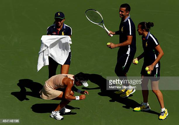 Ball people attempt to catch a honey bee in front of Kimiko DateKrumm of Japan during her women's singles first round match match against Venus...