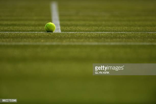 A ball sits on the grass before Spain's Garbine Muguruza plays against Belgium's Alison Van Uytvanck in a women's singles second round match on the...