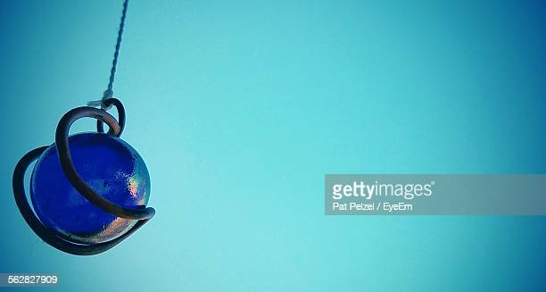 Ball With Metal Hanging Against Blue Background