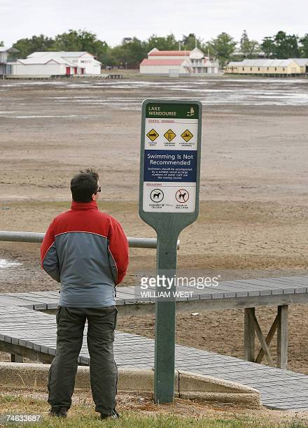 Photo taken, 16 November 2006, shows a man looking out towards the empty boatsheds lining the side of the empty Lake Wendouree in the centre of the...