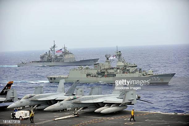hmas ballarat of the royal australian navy cruises alongside us navy ships. - uss george washington stock photos and pictures