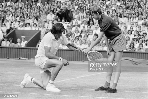A ballboy hands back Ilie Nastase's racket after the Romanian tennis player took a fall during his Men's Singles semifinal match against Manuel...