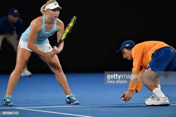 A ballboy lifts a moth from the court as Australia's Daria Gavrilova waits to receive serve from Belgium's Elise Mertens during their women's singles...