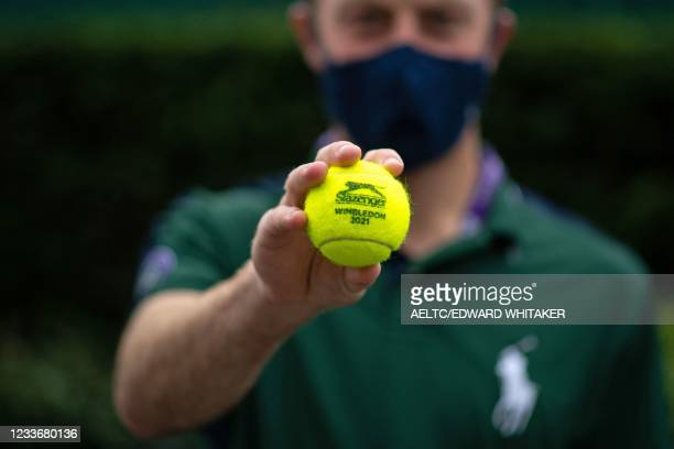 Ballboy poses for a photograph holding a branded Wimbledon 2021 tennis ball at The All England Tennis Club in Wimbledon, south-west London, on June...