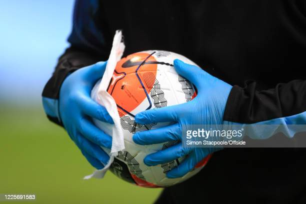 Ballboy wearing protective gloves wipes down the ball with disinfectant during the Premier League match between Manchester City and Newcastle United...