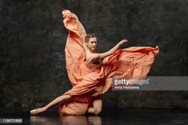 ballerina. a young ballet dancer dressed in a long peach dress, pointe shoes with ribbons. the girl performs an elegant, graceful dance movement. beautiful classic ballet. advertising ballet school. - actor stock pictures, royalty-free photos & images