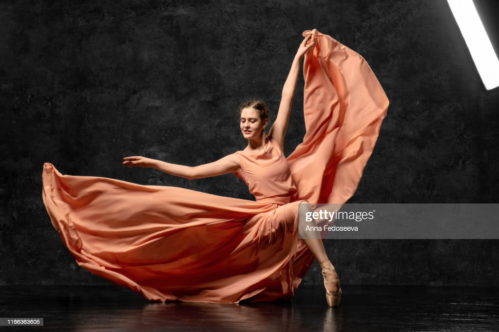 Ballerina. A young ballet dancer dressed in a long peach dress, pointe shoes with ribbons. The girl performs an elegant, graceful dance movement. Beautiful classic ballet. Advertising ballet studio. : Stock Photo