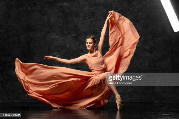 ballerina. a young ballet dancer dressed in a long peach dress, pointe shoes with ribbons. the girl performs an elegant, graceful dance movement. beautiful classic ballet. advertising ballet studio. - little girls up skirt stock pictures, royalty-free photos & images