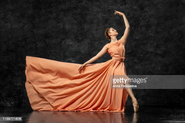 ballerina. a young dancer dressed in a long peach dress, pointe shoes with ribbons. performs a graceful, graceful dance movement. beautiful classic ballet. advertising ballet studio. volumetric photos - long dress stock pictures, royalty-free photos & images