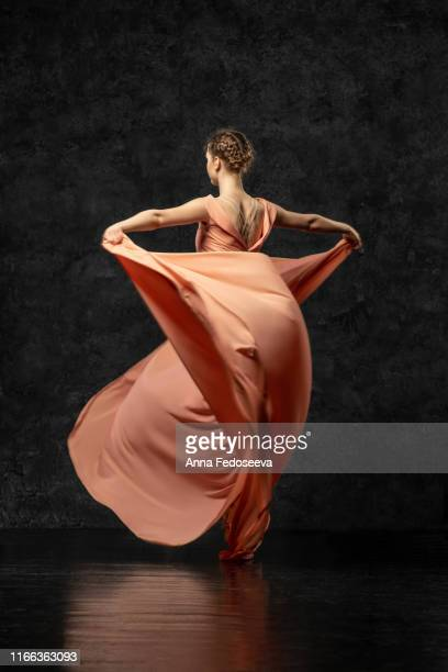 ballerina. a young dancer dressed in a long peach dress, pointe shoes with ribbons. performs a graceful, graceful dance movement  which is visible from the back. beautiful classic ballet. - vestido comprido imagens e fotografias de stock