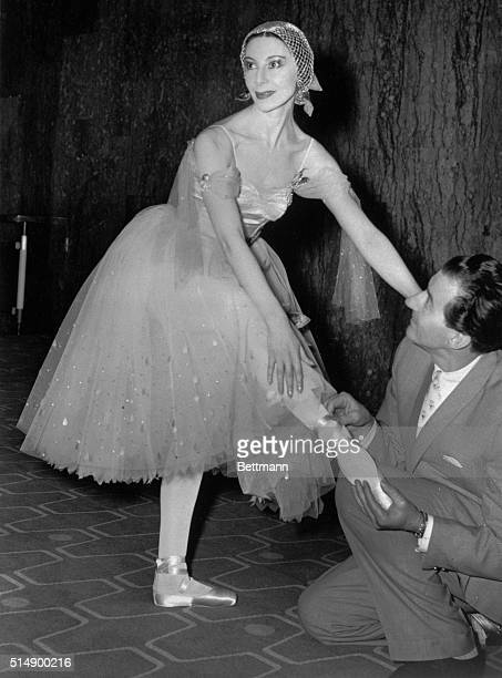 Ballerina Alicia Markova is aided during a rehearsal of Where the Rainbow ends, as Anton Dolin, who has a role in the production, adjusts one of her...