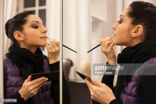 Ballerina applying lipstick before going on stage