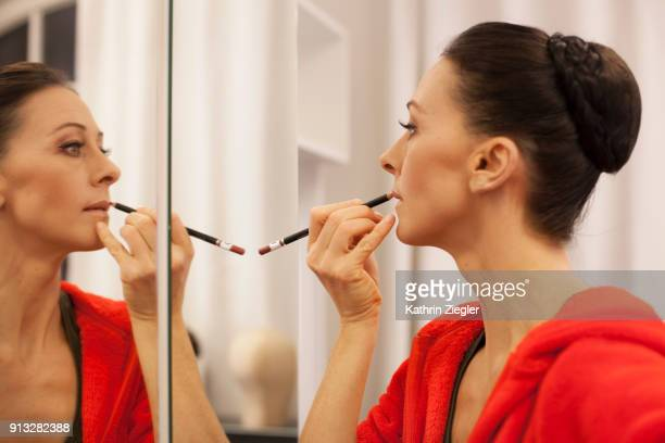Ballerina applying lipstick before going on stage, reflected in the dressing room mirror