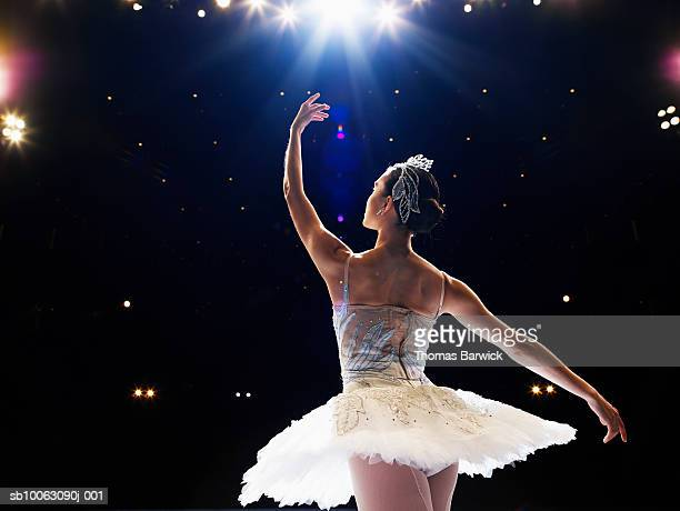 Ballerina dancing on stage, arm raised, rear view