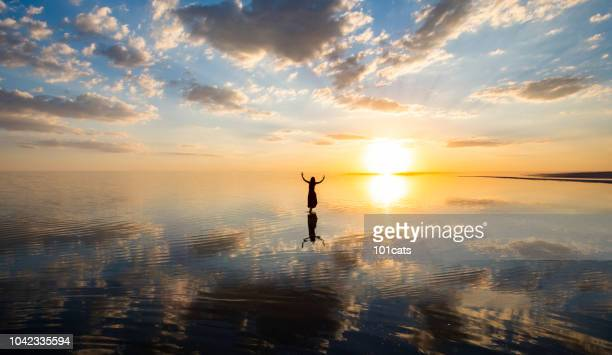Ballerina dancing on the lake at sunset.