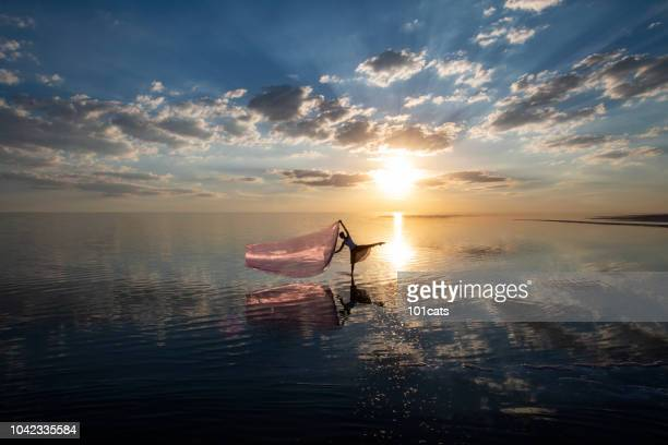 Ballerina dancing on the lake at sunset with red tulle.