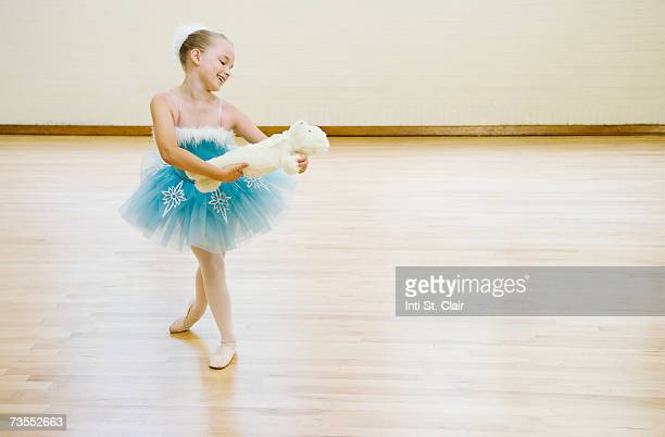 ballerina (8-9) dancing with teddy bear, smiling, close-up - dancing bear immagine foto e immagini stock