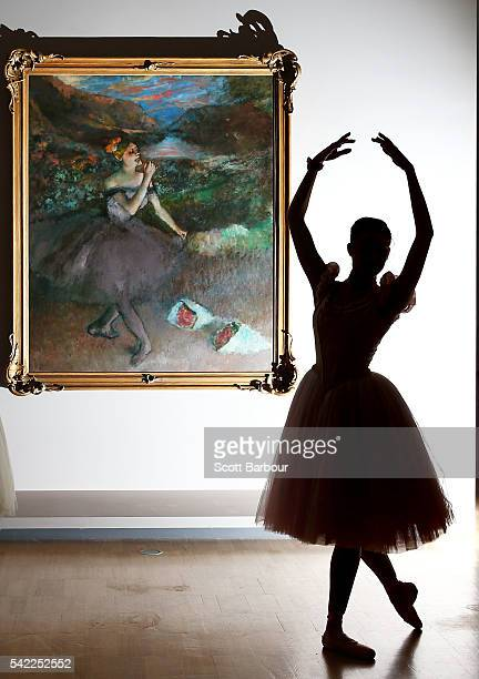 Ballerina from The Australian Ballet is silhouetted as she poses next to one of Edgar Degas' iconic ballet dancer paintings 'Dancer with Bouquets'...