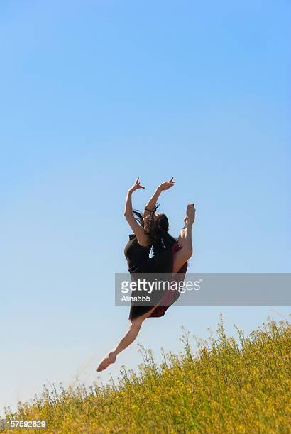 ballerina in a black dress jumping outdoors - alina stock pictures, royalty-free photos & images