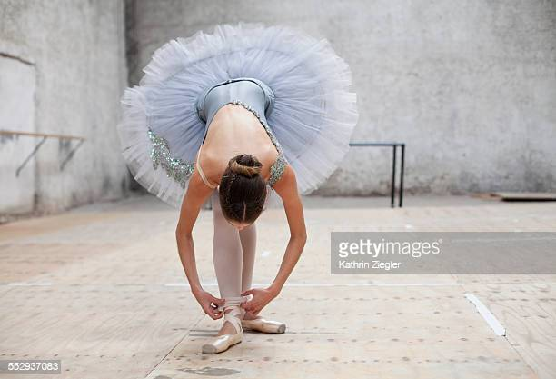ballerina in a tutu adjusting her pantyhose