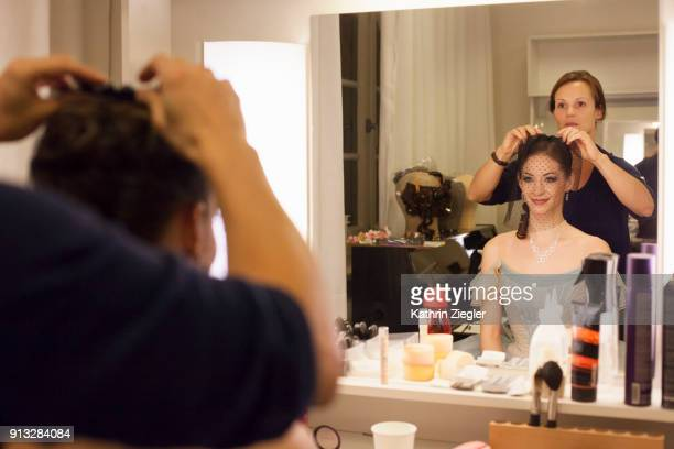 Ballerina in dressing room getting her hair and makeup done by makeup artist, reflected in the mirror