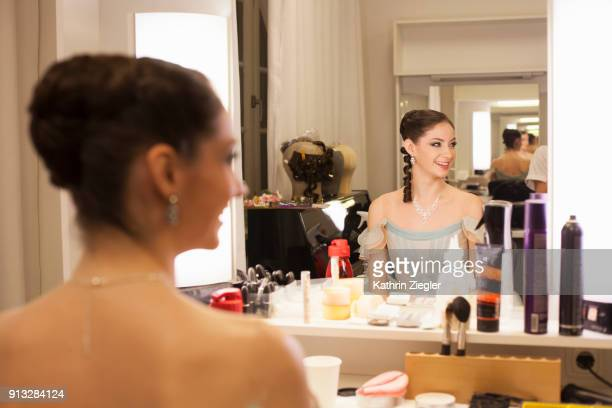 Ballerina in dressing room reflected in the mirror