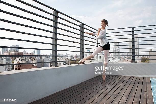ballerina in pointe shoes exercising on sun deck