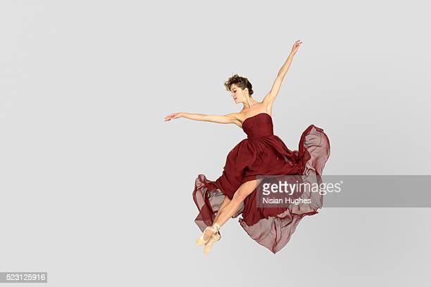 Ballerina in silk dress performing jump with crossed feet