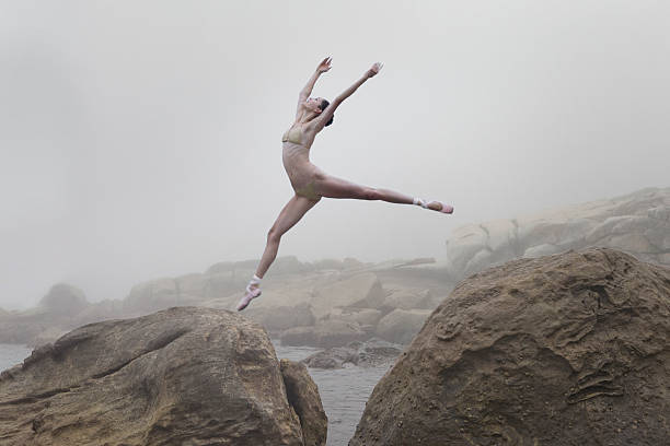 Ballerina leaping from one rock to another