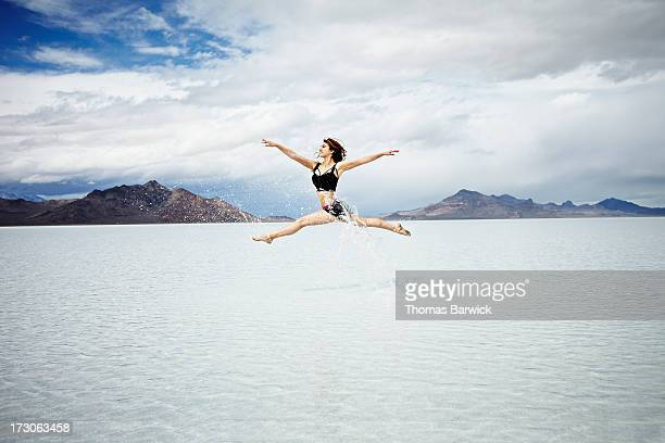 Ballerina leaping in mid-air over lake