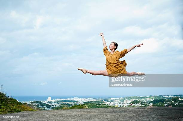 Ballerina leaping in the air on a roof, Okinawa, Japan