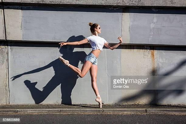 ballerina leaping on sidewalk on points - solo una donna giovane foto e immagini stock