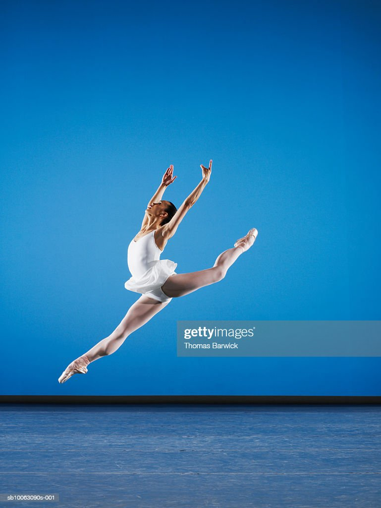 Ballerina leaping on stage, side view : Stock Photo