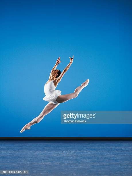 ballerina leaping on stage, side view - ballet dancer stock pictures, royalty-free photos & images