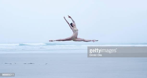 Ballerina leaping on the beach