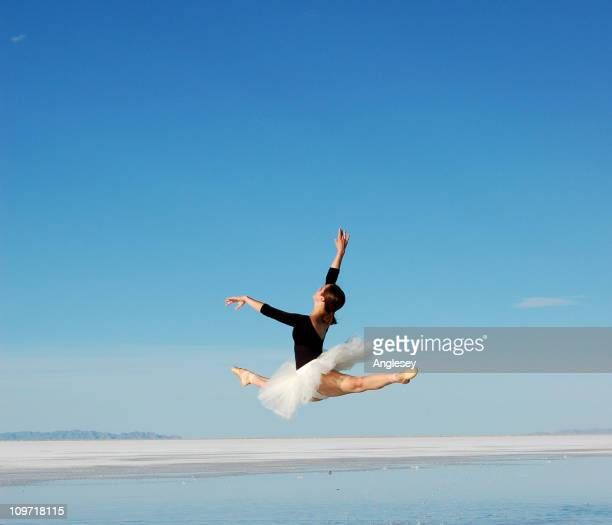 Ballerina leaping over water on the salt flats on a blue sky