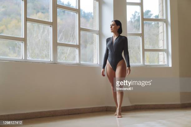 ballerina looking through window while standing in dance studio - rehearsal stock pictures, royalty-free photos & images