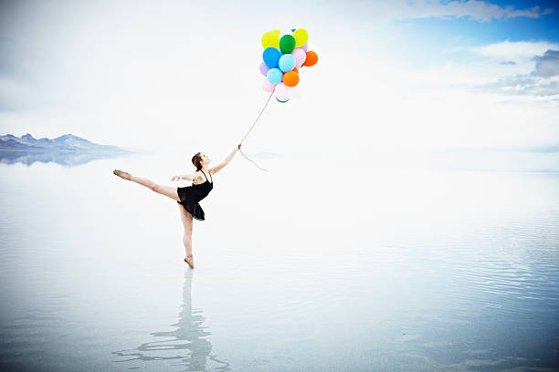 Ballerina On Tip Toe In Water Holding Balloons Wall Art