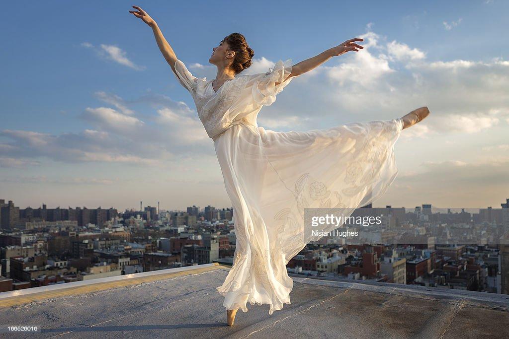 Ballerina performing Arabesque on roof : Stock Photo