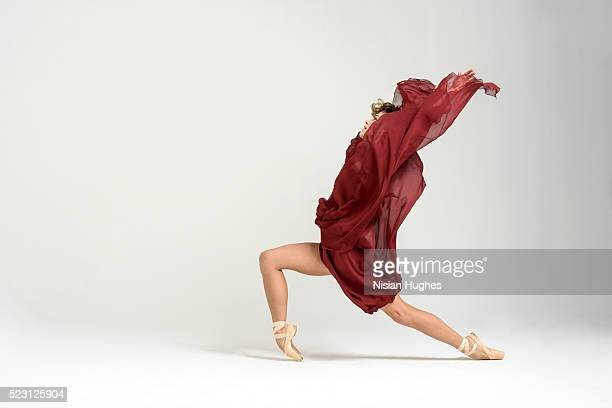 Ballerina performing lunge on pointe in studio